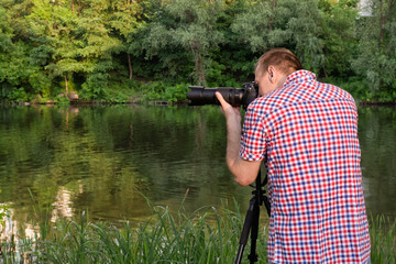 Photographer is shooting on the river bank, summer