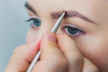 Woman with blue eyes getting makeup on brows