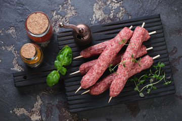 Black wooden cutting board with raw cevapi or cevapcici sausages on wooden skewers, brown stone background, view from above