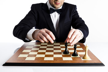 mart man in a dark suit playing whites chess is about to give checkmate to  black king.