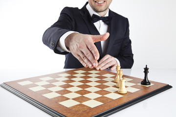 Game over. Smart man in a dark suit playing whites has just won a game of 
