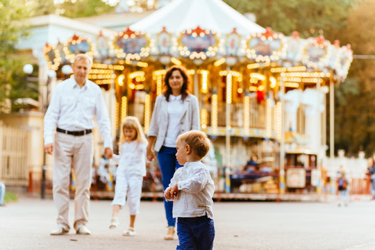 Cute toddler boy running in amusement park with her family on background. Family vacation concept.