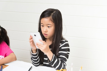 Cute asian girl kid playing smartphone and found something which surprised her while searching on the internet during her study time on light background with friends and copy space