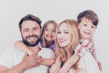 Family photo portrait. Four relatives are hugging on the white background, smiling, at home, blond mum is piggy backing the cute small son