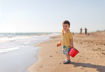 Boy carrying bucket and shovel on beach