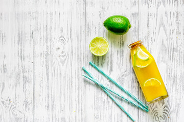 Bottle of fresh lemonade and fruits on grey table background top view copyspace