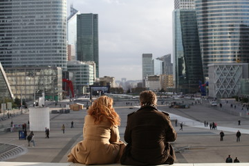 Rear view of couple sitting together and looking at city