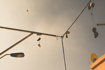 Low Angle View Of Shoes Hanging Metallic Poles