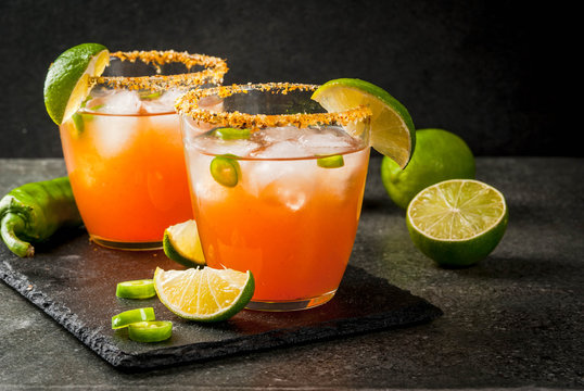 Alcohol. Traditional Mexican South American cocktail. Spicy michelada with hot jalapeno peppers and lime. On a dark stone table. Copy space