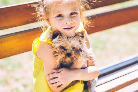 Little beautiful girl is walking in the park with a dog
