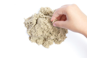 Child playing with kinetic sand. Hand of the child in the sand close up on a bright background