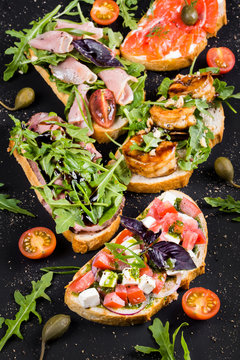 Brushetta set for wine. Variety of small sandwiches with prosciutto, tomatoes, parmesan cheese, fresh basil