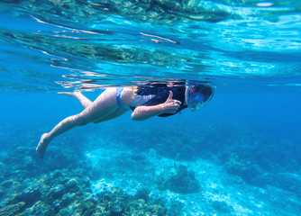 Woman snorkeling in blue water. Snorkel shows thumb in full face mask.