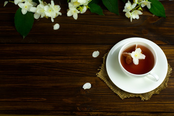 Tea with jasmine in a white mug on a wooden table