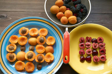 plates with apricots and cherries and colander full of berries