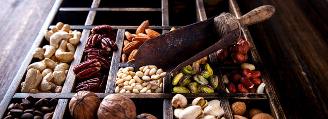 Nuts Mixed in a Wooden Vintage Box.Assortment, Walnuts,Pecan,Peanuts,Almonds,Hazelnuts,Macadamia,Cashews,Pistachios.Concept of Healthy Eating.Vegetarian.selective focus.
