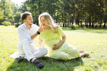 Pregnancy couple laughing and eating chocolate candies in a park on the grass.