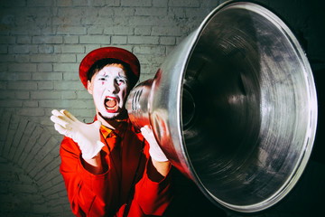 Mime took a metal lampshade and pretends to shout into the shout
