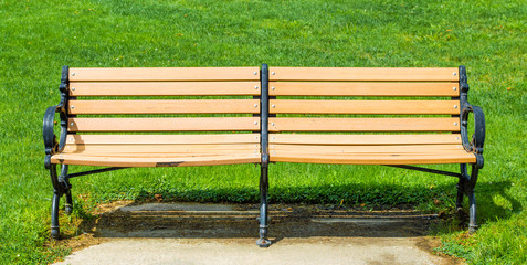 empty varnished double bench outdoors in park