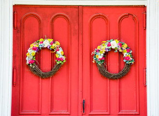 weathered vibrant red double doors with wreaths of dried flowers