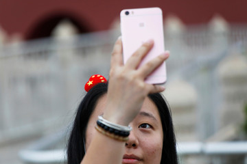 A woman with a heart shaped pin in Chinese national colours in her hair, takes a picture of herself at the Tiananmen Gate in Beijing