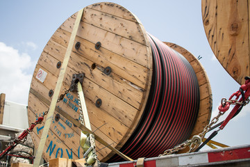A reel of cable being hauled on a truck.