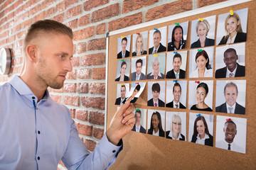 Businessman Selecting Candidates Photo On Corkboard