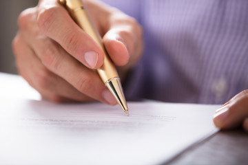 Businessperson's Hand Signing Document With Pen