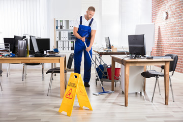 Male Janitor Cleaning Floor With Mop