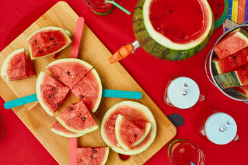 Close up summer outdoor table with red sheet and watermelon style drinks and slices for watermelon party