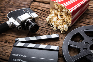 Movie Camera With Clapper Board And Popcorn On Wood