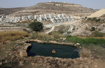 An Israeli youth swims in a natural spring water pool to cool off on a summer day near outskirts of Jerusalem