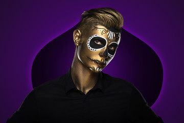 The guy with the painted golden face for Halloween. Masquerade Party. Night festivities dressed as zombies. Face art