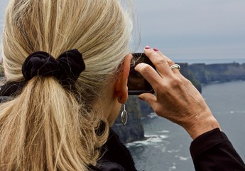 Mature Woman Photographs Cliffs of Moher - a mature blond female tourist takes photographs at the Cliffs of Moher, Ireland during a gray spring day in May of 2017
