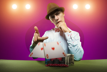 Beautiful young man on a beautiful background playing poker. Good luck in card games on the big money. Looking at the camera