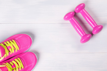 Female set for playing sports, with pink dumbbells, on a light wooden floor