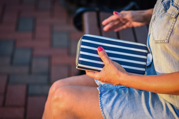 woman sitting on bench outside holding wallet