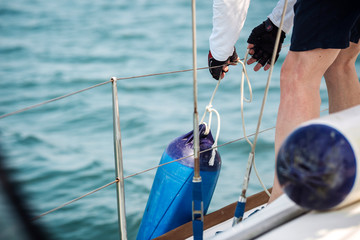 Sailor tied fenders on a yacht during the mooring to the shore.