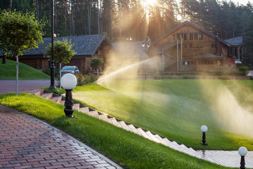 Watering the lawn near wooden house  on a summer morning