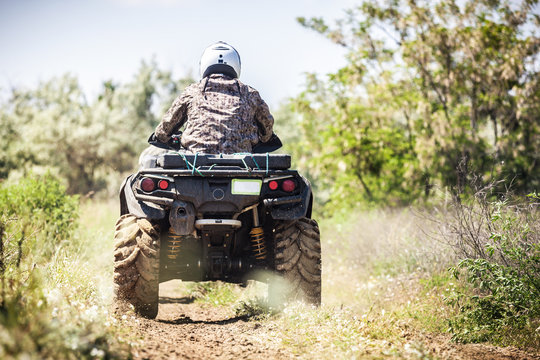 Back view of quad bike  riding along a country road.