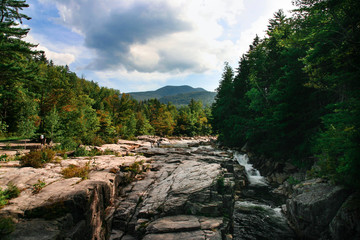 River in New Hampshire with rocks, trees and clouds