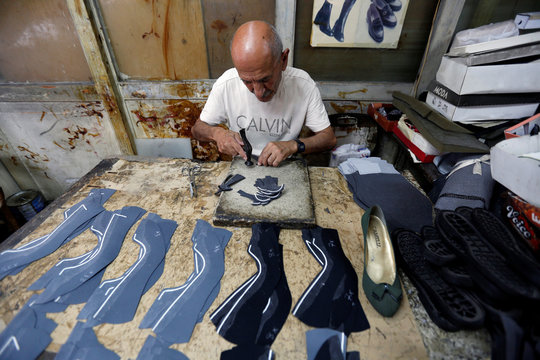 Man works on leather pieces to create women's shoes at Camelia shoe factory in Beirut