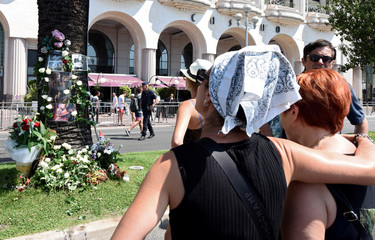 People look at photos of victims on the Promenade des Anglais as part of the commemorations of the July 14 fatal truck attack on the Promenade des Anglais in Nice