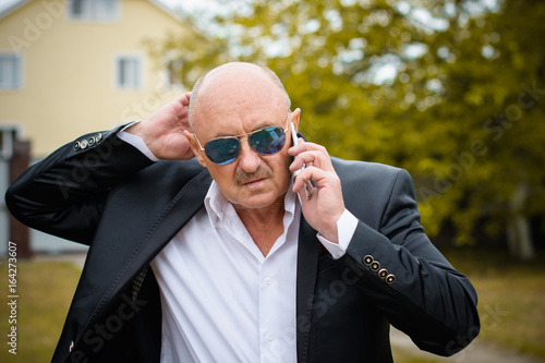 Portrait Stylish Mature Men In White Shirt And Jacket And Blue Sunglasses  Using Smartphone. Serving