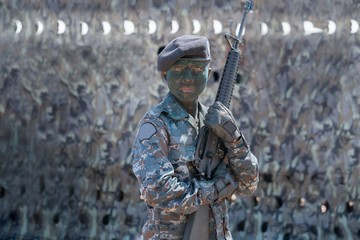 conceptual young soldier face with jungle camouflage paint and automatic rifles in hands