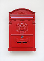 Traditional old English red postbox mounted on white wall.