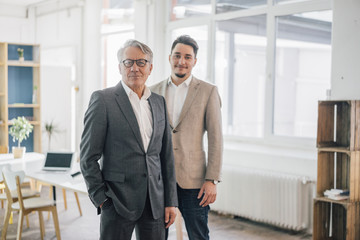 Portrait of confident old and young businessman in office