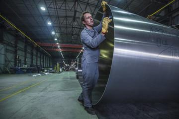 Worker labeling metal in factory