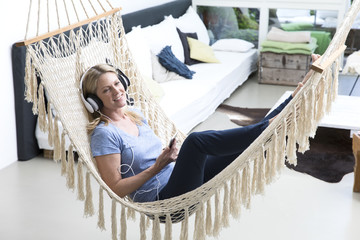 Relaxed woman at home lying in hammock listening to music