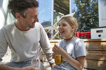 Happy father and daughter with drinks at an outdoor cafe
